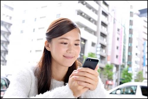 携帯を見る女性の画像