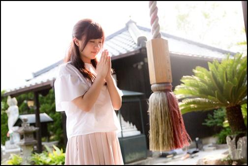 神社でお祈りする女子の画像