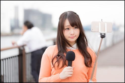 自撮り棒で自撮りする女性の画像