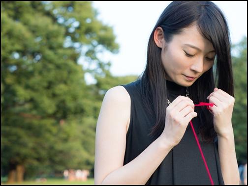 赤い糸を持つ女性の画像