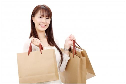 女性が紙袋、お土産を持つ画像