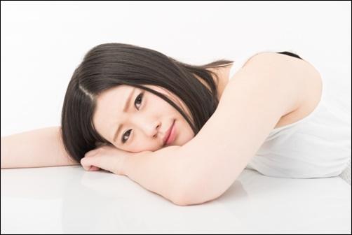 横になりながらこちらを見る美人女性の画像