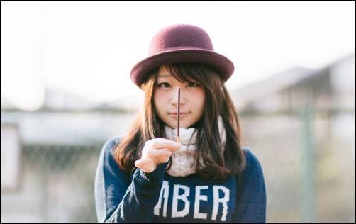 最期の1ッ本とポッキーを掲げる女性の画像
