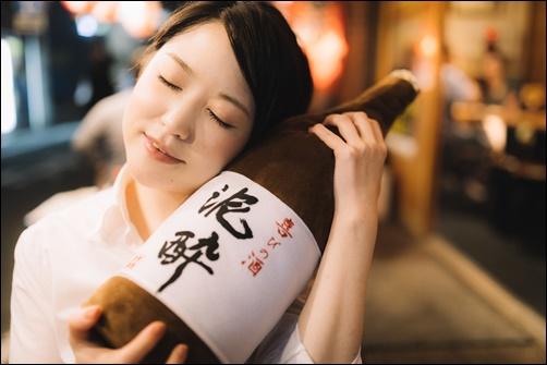お酒を持って笑顔の女性の画像