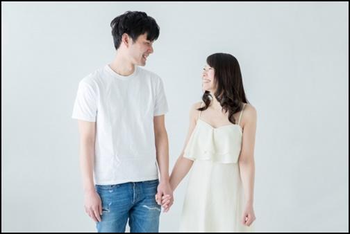 手つなぎで向き合っているカップル画像
