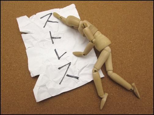 ストレスと書かれた紙と倒れている人形の画像