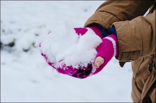 手袋をして雪を持つ女性の画像