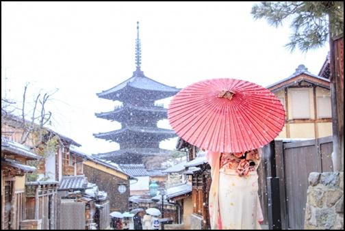 雪の京都の中を着物を着た女性が傘をさして歩く画像