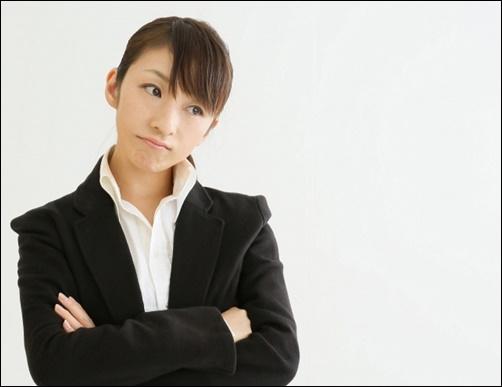女子就職活動学生がスーツ姿で腕を組んで考える画像