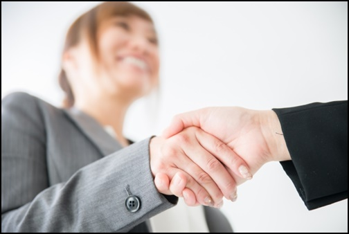 OLとサラリーマンが握手している画像