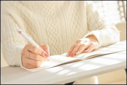 ノートにメモする女性の画像