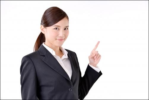 スーツ姿で指差しする女性の画像