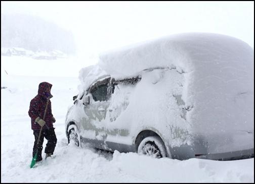 車に積もった積雪を取っている画像