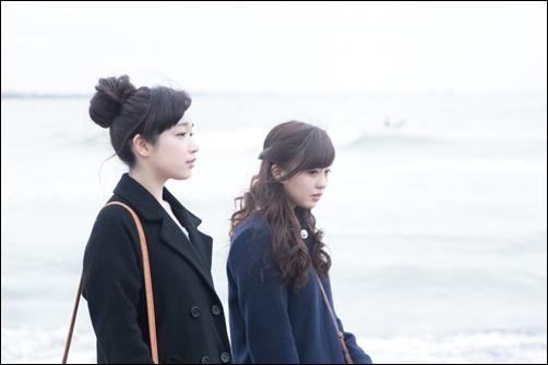 浜辺を歩く女性二人の画像
