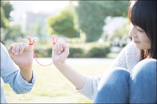 彼氏に赤い糸を繋いで結婚を追求する女性の画像