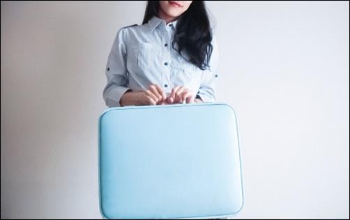 女性がスーツケースを持つ画像
