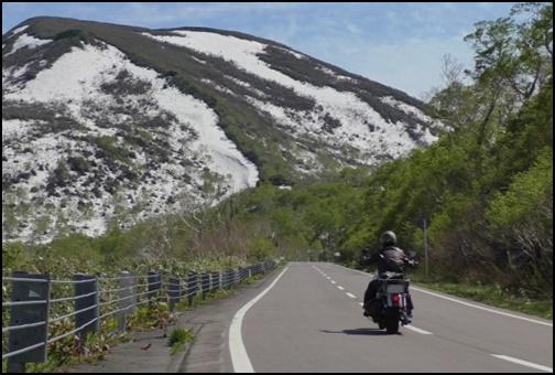 雪山と道路をバイクで走る画像
