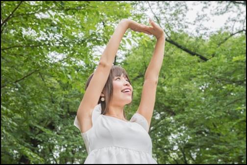 新緑の中で伸びをする女性の画像