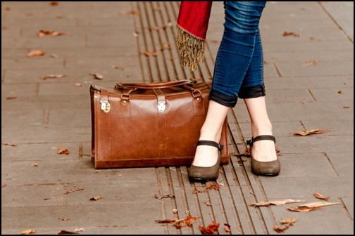 バックを足元に置いた旅行中の女性の画像