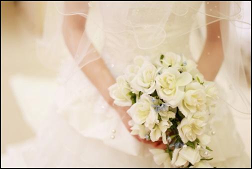 ウエディングドレス姿で白い花のブーケを持つ女性の画像