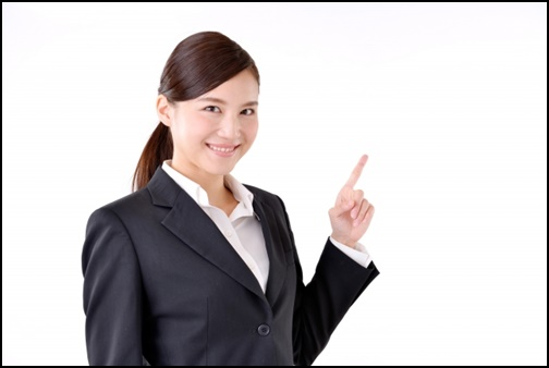 笑顔で指差しする女性の画像
