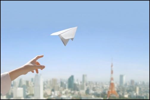 紙飛行機を飛ばす画像