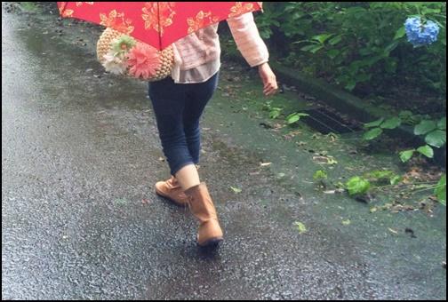 雨の中傘をさしで歩く女性の画像