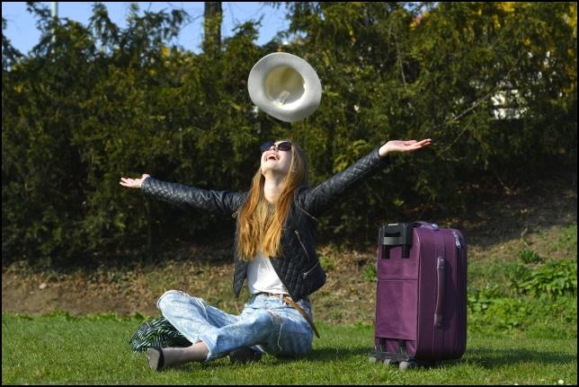 旅行している女性が芝生の上で休憩している画像