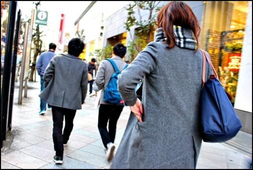 コートを着て外を歩く女性の画像