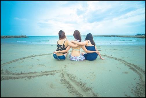 女性3組がビーチに座っている画像