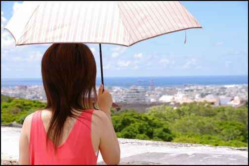 日傘を持つ女性の後ろ姿の画像