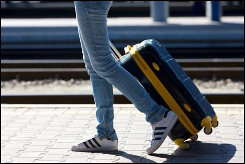 旅行する女性の足元とキャリーバックの画像