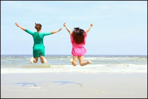 ビーチでジャンプする女性2名組の画像