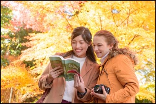 外国人に案内している日本人女性の画像