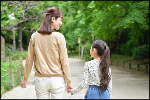 手を繋いで帰る親子の画像