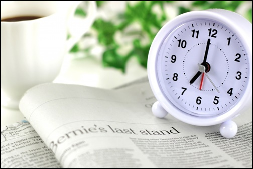時計と英語新聞の画像
