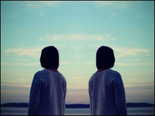 背を向け合う双子の画像
