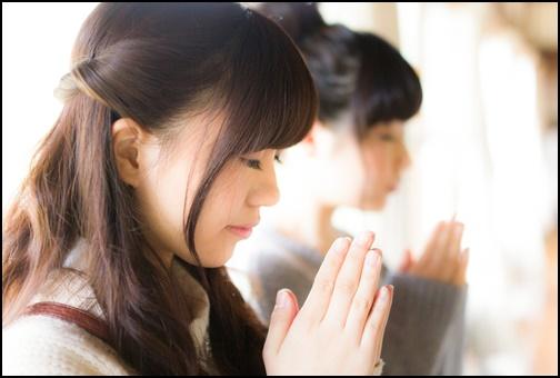 神社でお祈りする女性の画像