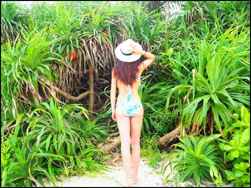 10月の沖縄で森林を見つめる水着姿の女性画像