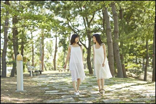 双子の姉妹が白いワンピースで森を歩く画像