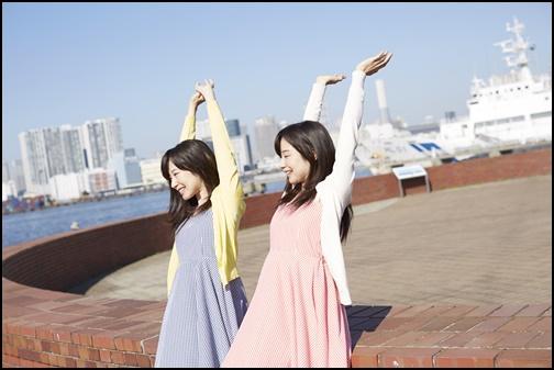 カーディガンを着た姉妹が沖縄でバンザイをしている画像