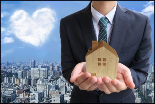 ハートの画像と家の模型を持つサラリーマンの画像