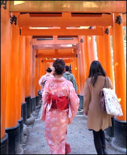 伏見稲荷神社の鳥居を歩く女性二人組の画像