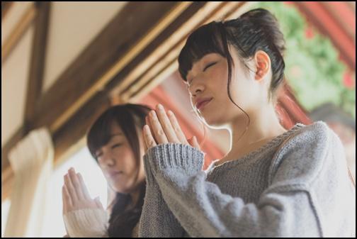 神社で参拝している女性二人組の画像