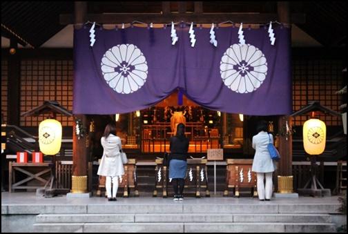神社で祈願する女性の画像