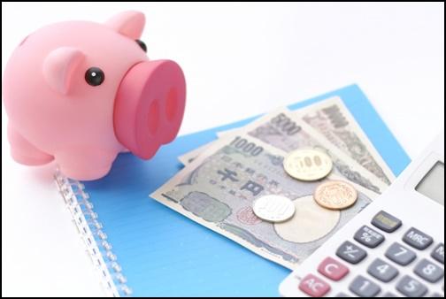 豚の貯金箱とお金の画像