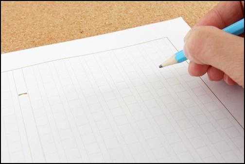 作文を書く為の原稿用紙と鉛筆と手の画像