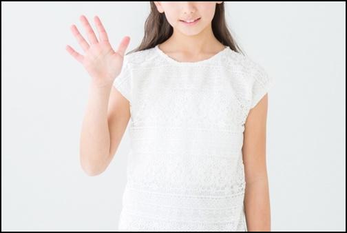 バイバイのポーズをする女性の画像