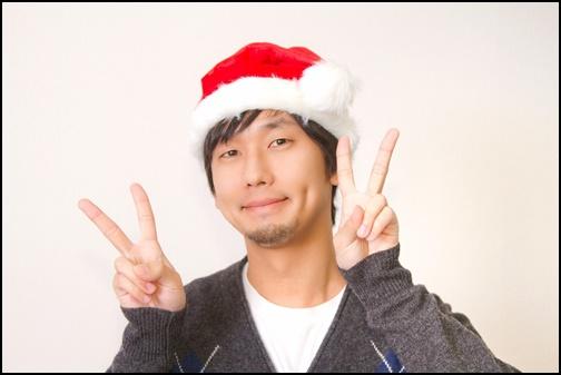サンタの帽子をかぶってピースする男性の画像