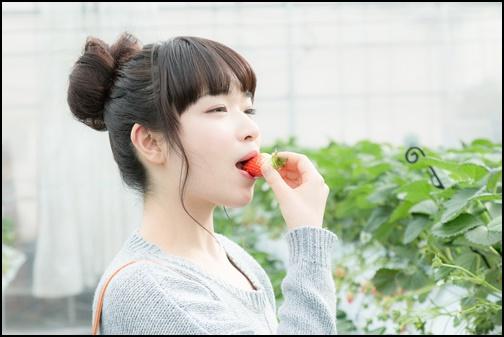 イチゴを食べる女性の画像